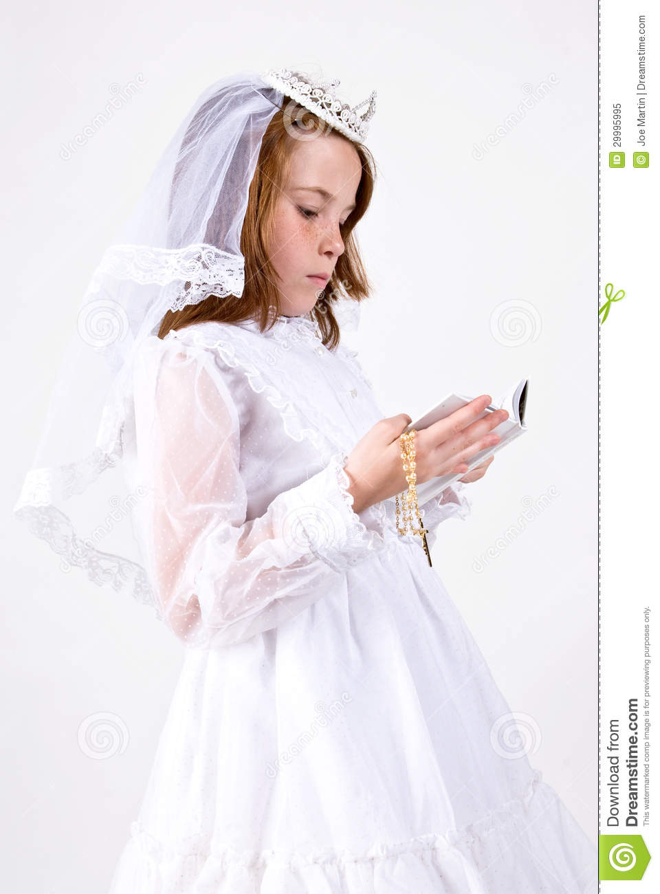 -up, from below, of a young girl smiling in her First Communion Dress