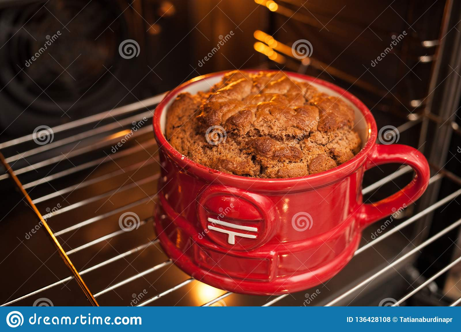 Close up a big lush ruddy mugcake in a red mug cooked in the oven. Cooking and cupcake recipes Realism