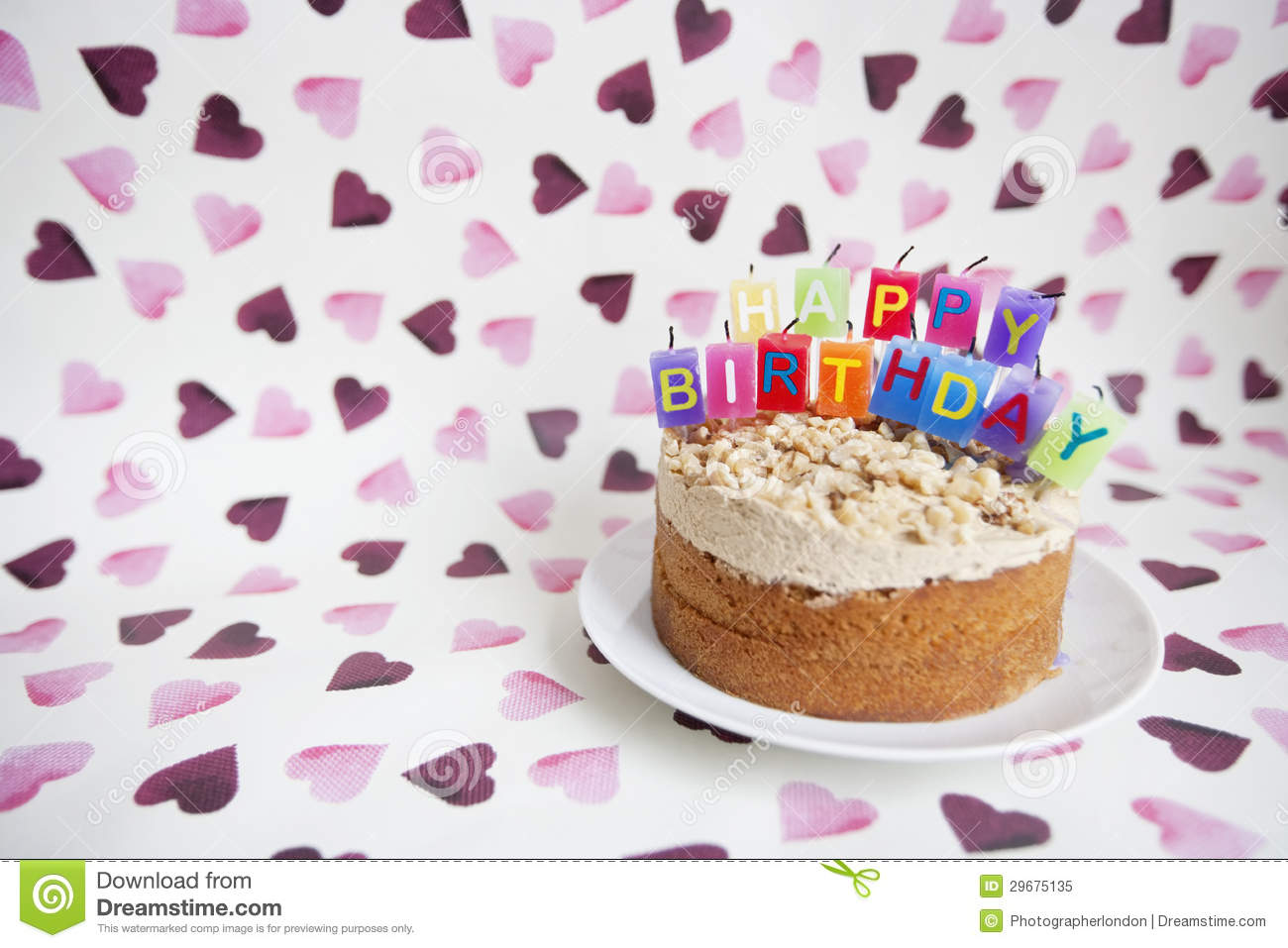 Close Up Of Birthday Candles On Cake Over Heart Shaped Background