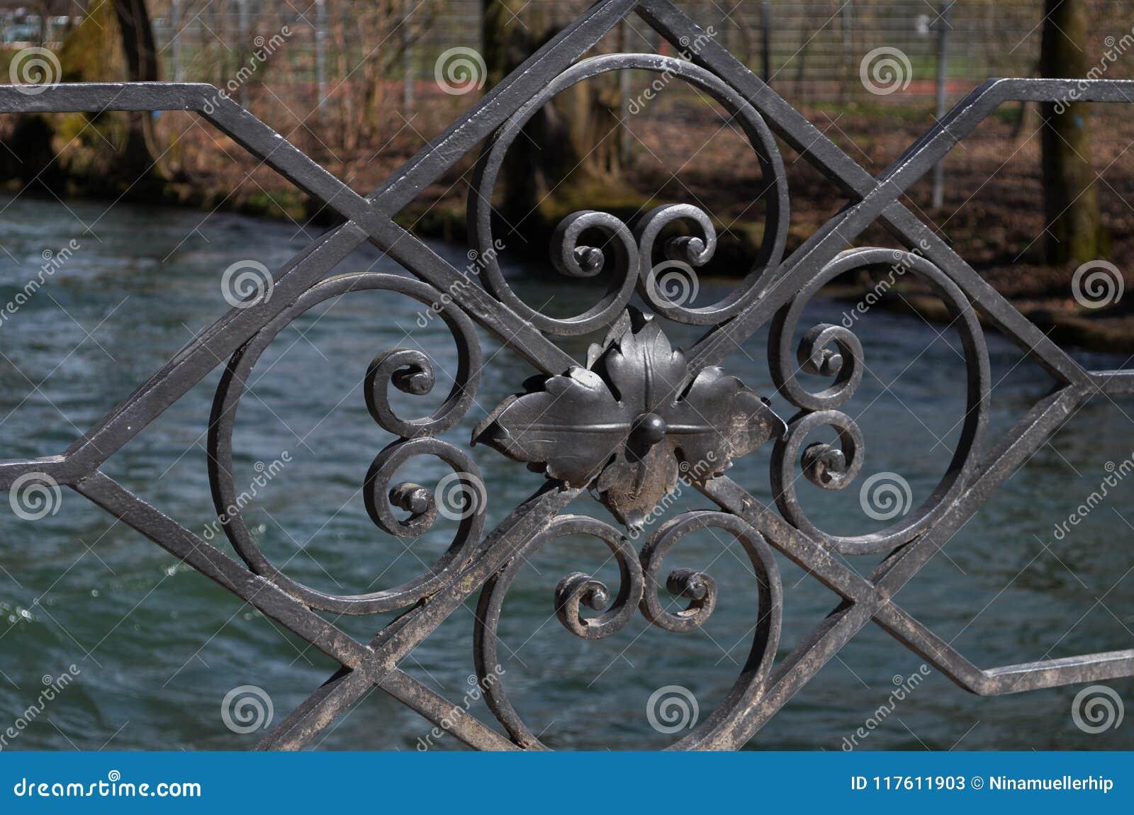 Close-up of the black iron ornaments of a bridge`s handrail