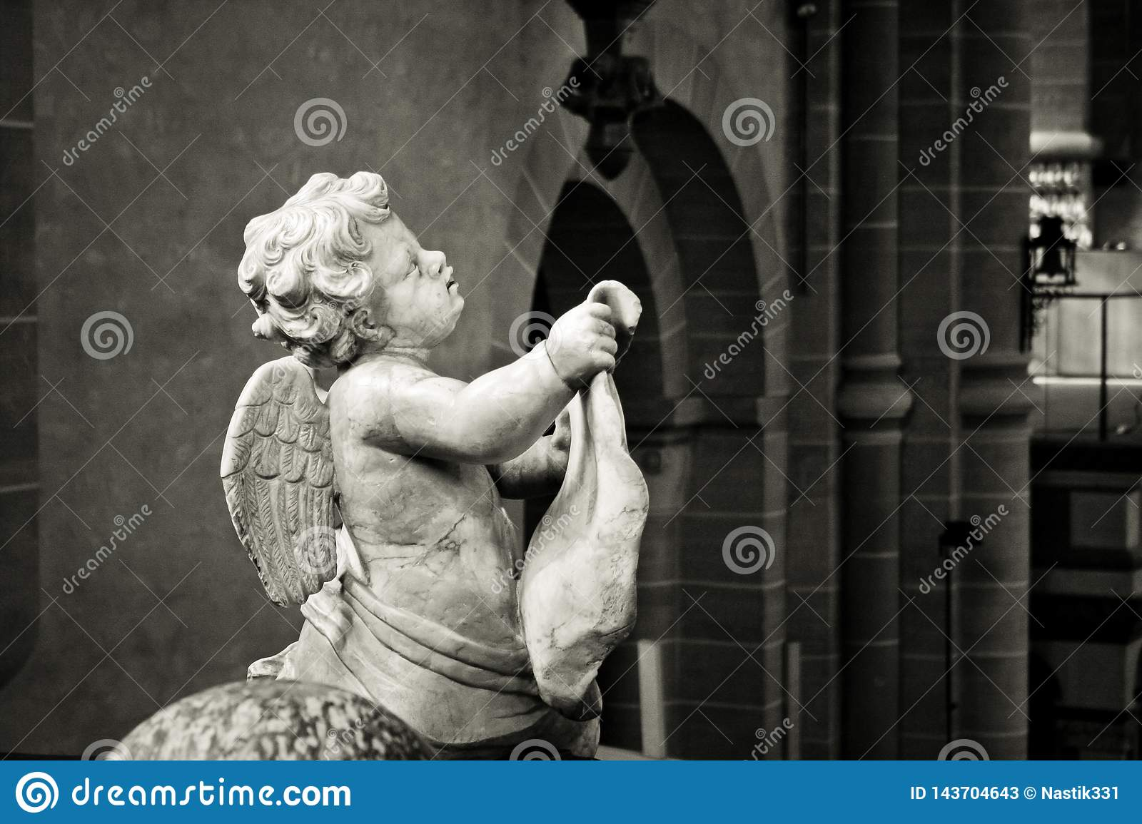 Close up black and white of an angel carved into stone