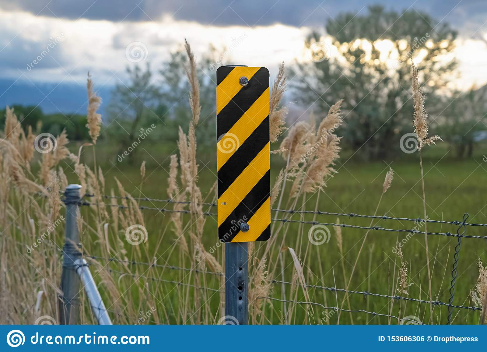 Close up of black and yellow diagonal stripes road sign beside barbed wire fence