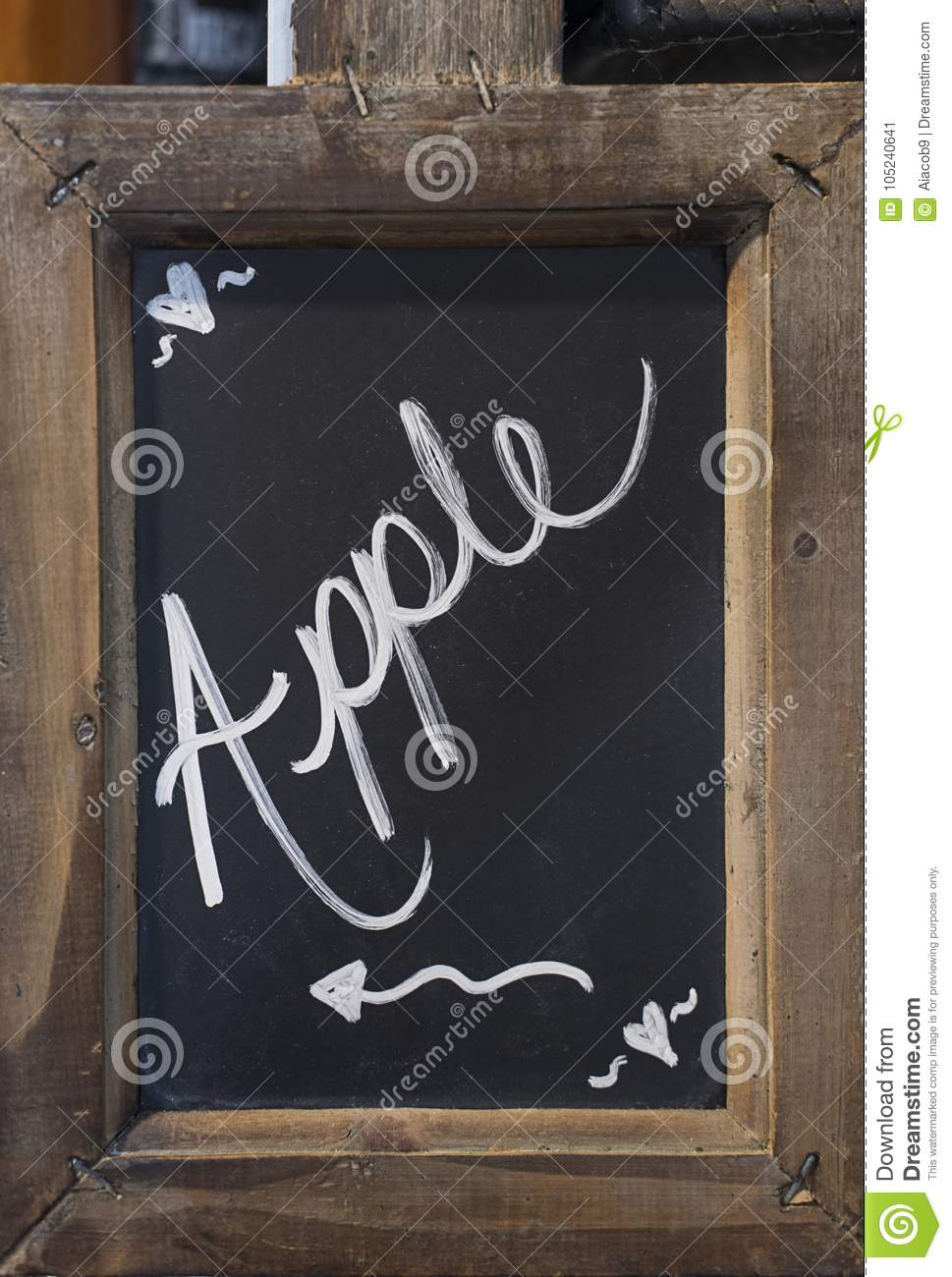 Close-up of blackboard with word `Apple` written on it with an arrow showing to the left, fixed in a wooden rustic frame