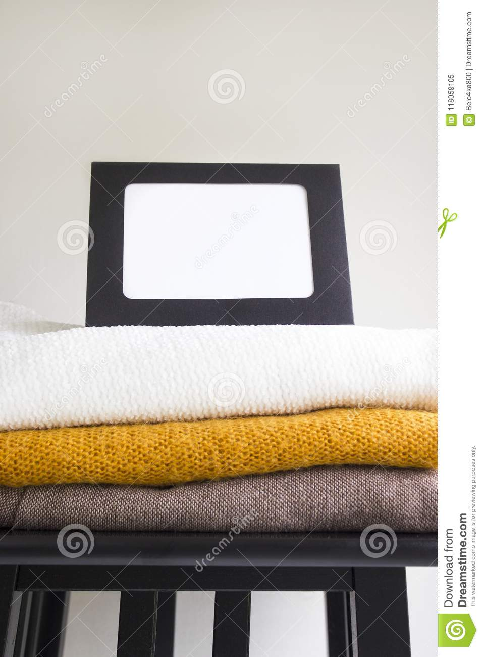 Close Up Blank Frame And Stack Of Folded Clothes On White