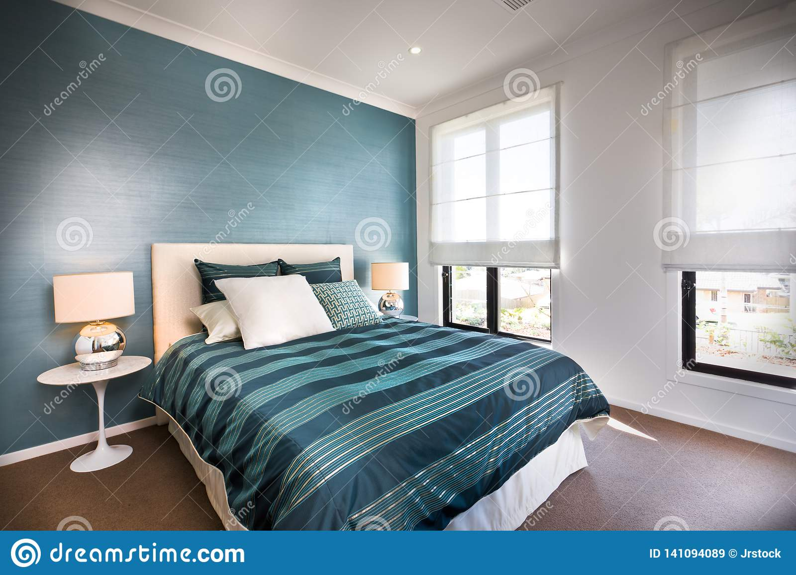 Close Up Of A Blue Decorative Bedroom With White Walls Stock