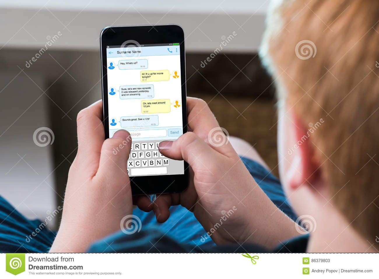 Boy Typing Text Message On Mobile Phone