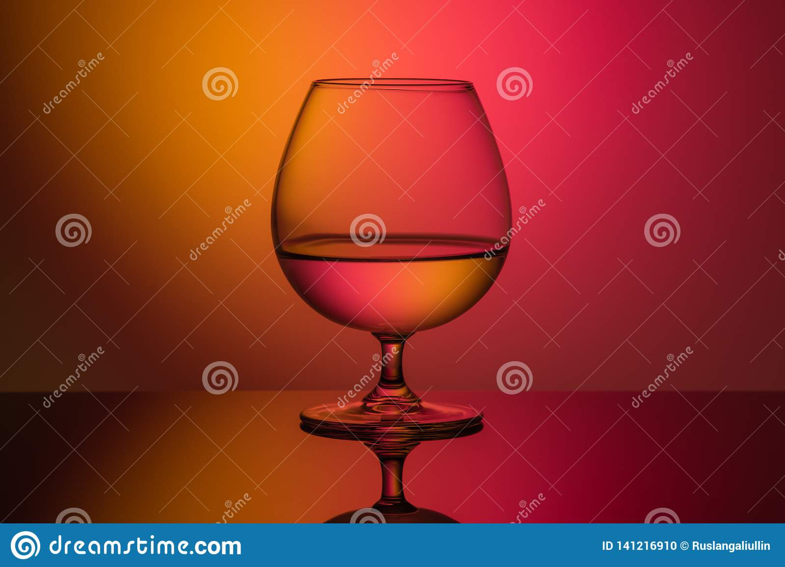 Close-up of brandy glass with liquid on orange red background