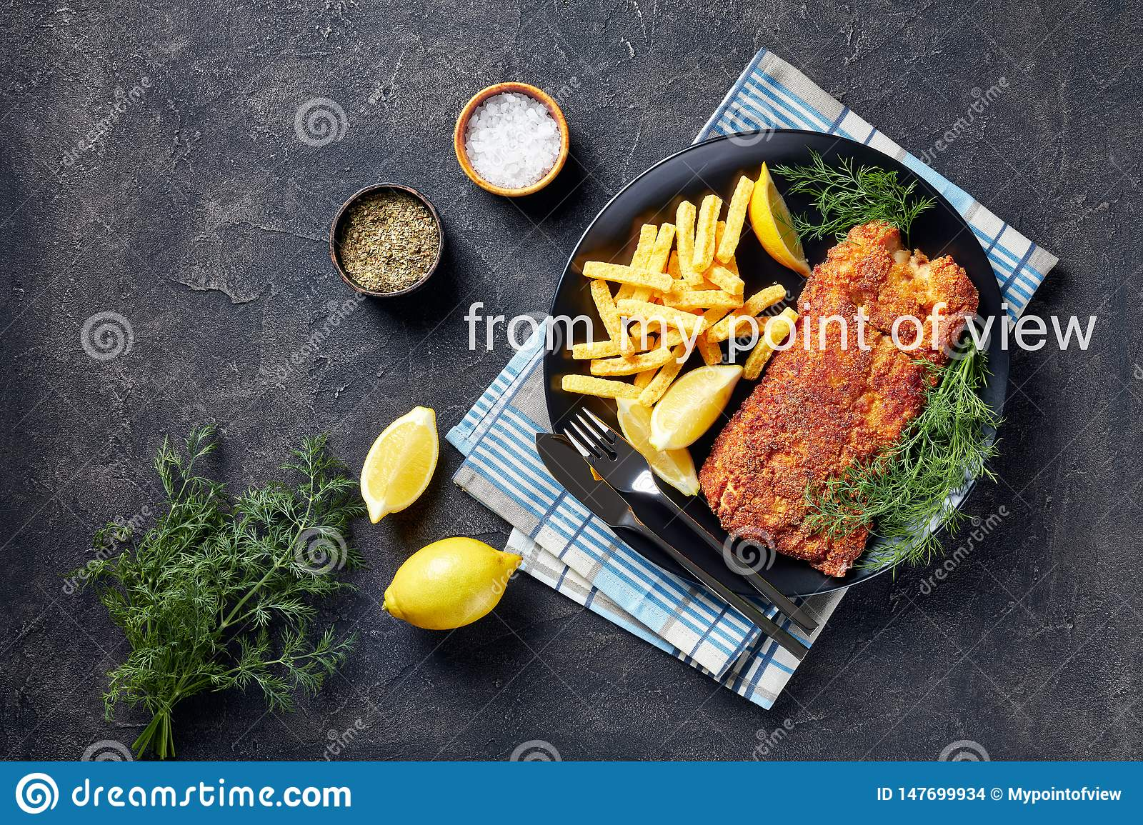 Close-up of Breaded hake fillet served with chips, fresh dill and lemon slices on a black plate on a white concrete table,
