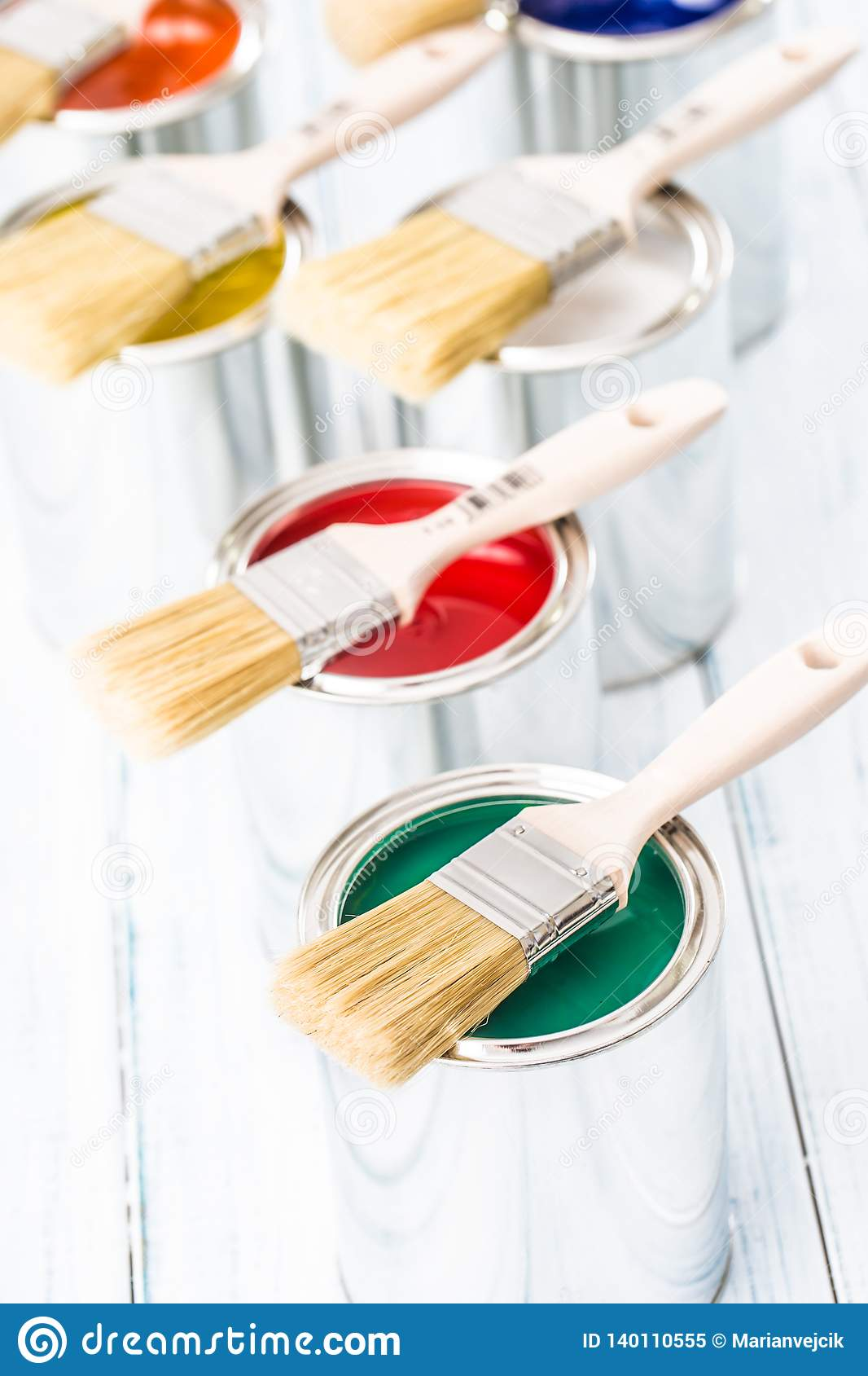 Close-up brushes lying on multicolored paint cans