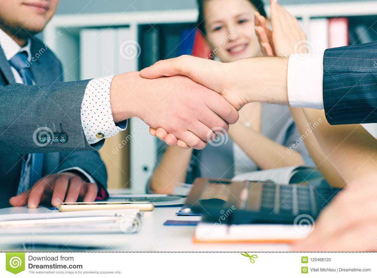 Close up business handshake on team meeting with clapping group of people blured in background at modern startup