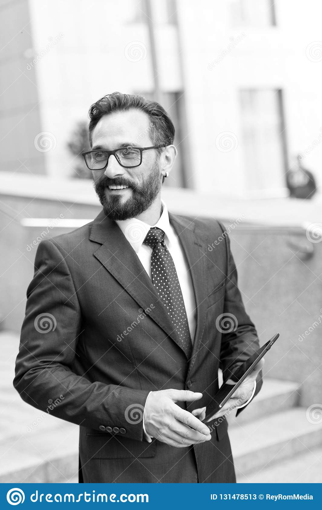 Close-up of business man using a digital tablet at work. Portrait of handsome bearded businessman at meeting outdoor