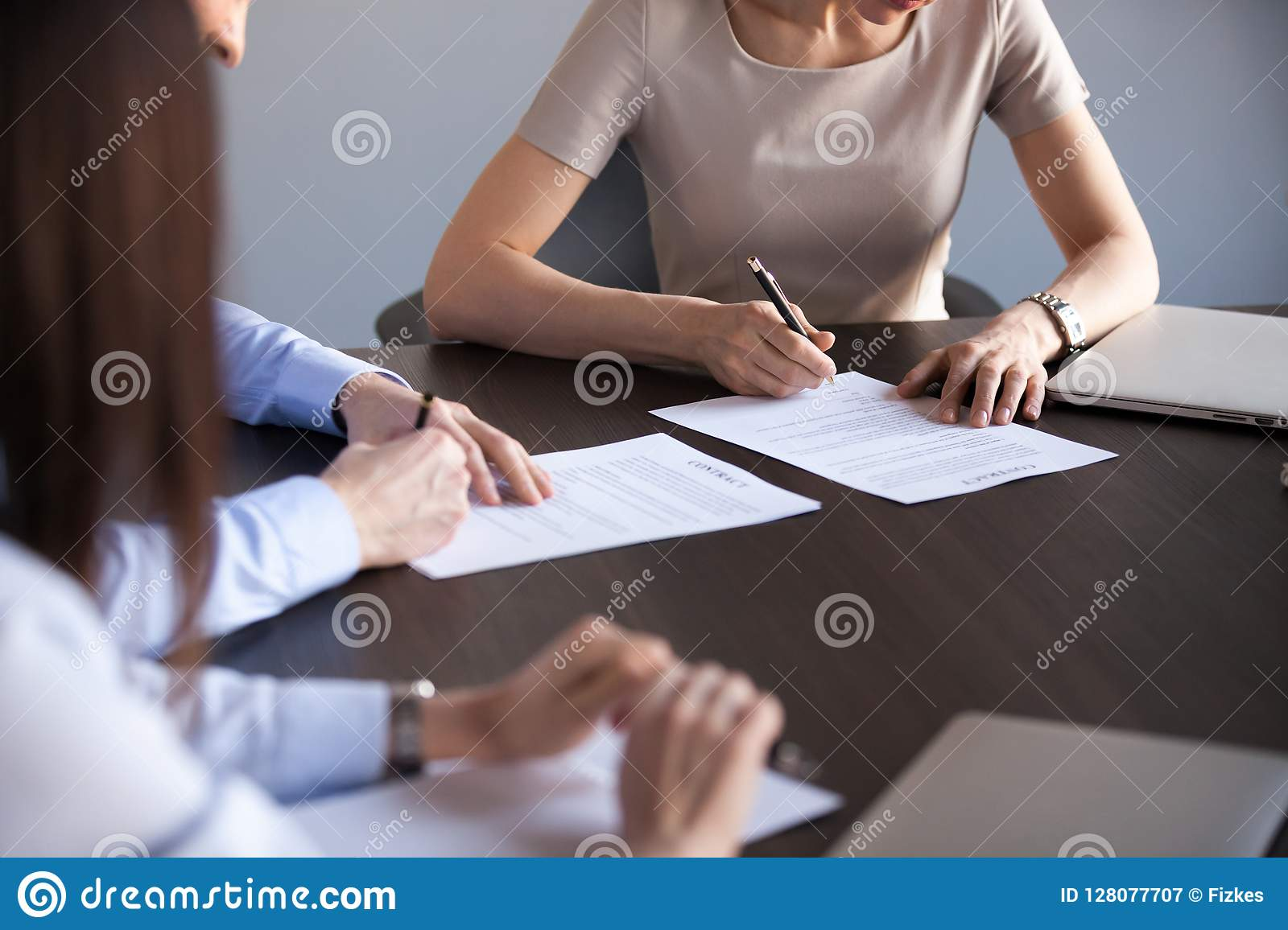 Close up of business partners man and woman signing contract