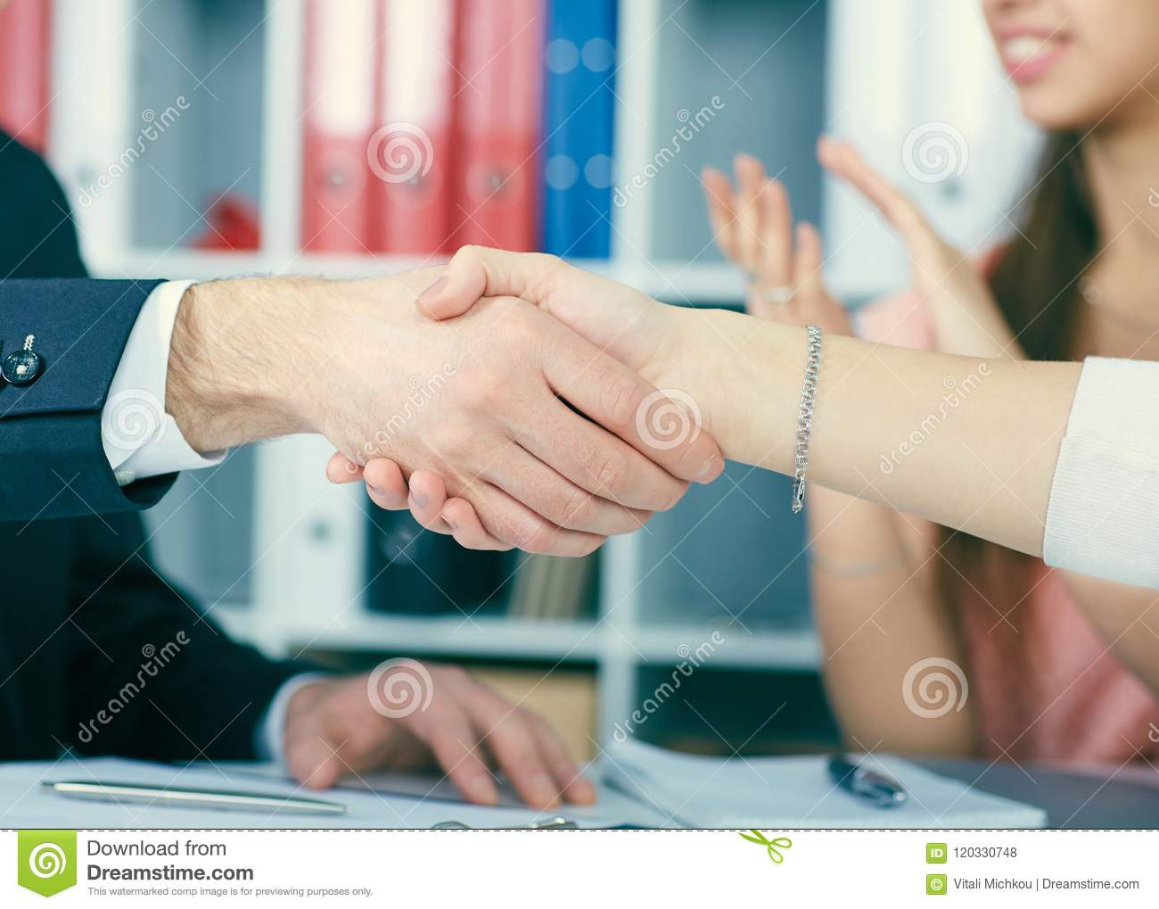 Close up business people handshake on team meeting with clapping group of people blured in background at modern startup
