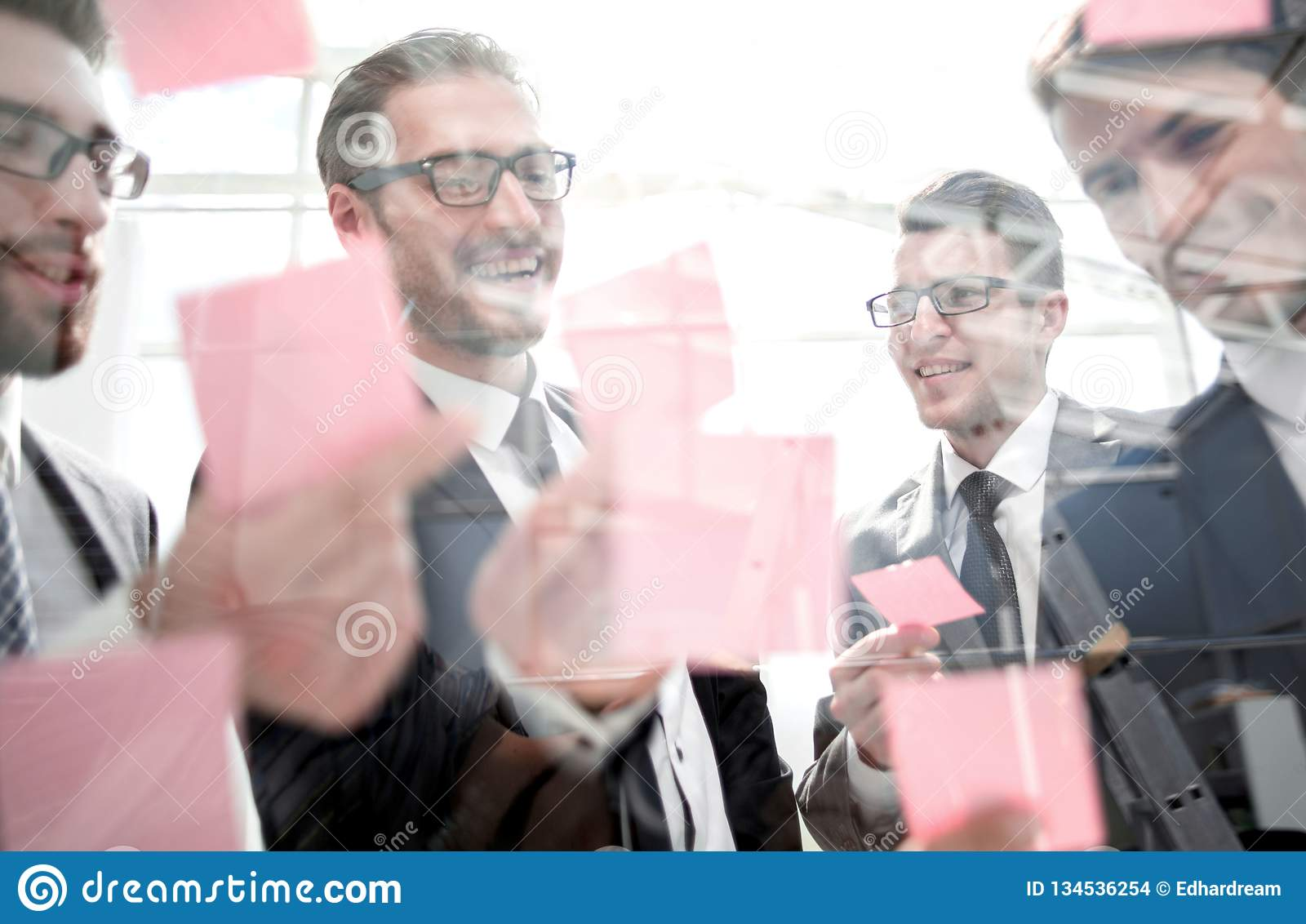 Close up.business team reading sticky notes on glass. The concept of a startup stock images