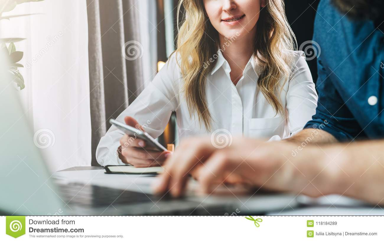 Businessman and businesswoman sitting at table in front of laptop and looking at monitor. Man is typing on laptop