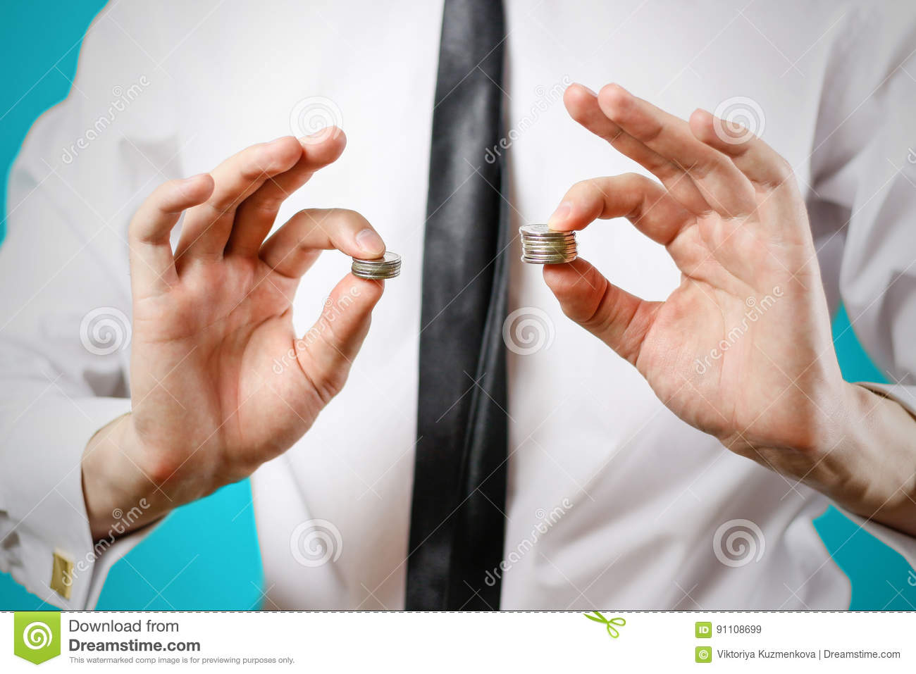 Close up. Businessman hands compare two piles of coins of differ