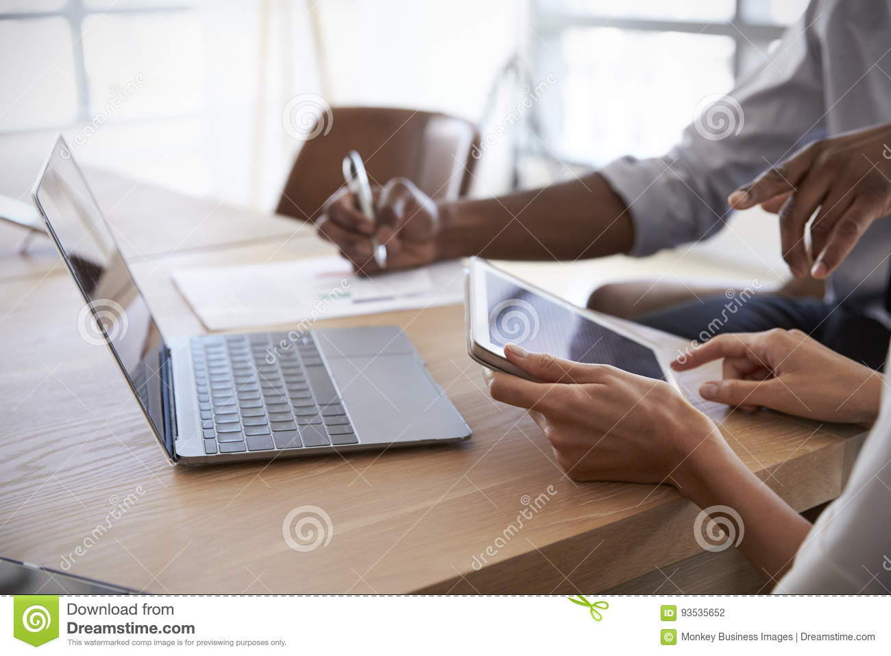 Close Up Of Businesspeople Working On Laptop In Boardroom