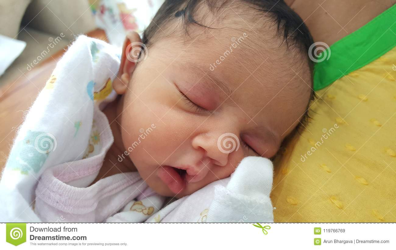 Beautiful indian asian new born baby girl having hair on forehead with closed eyes head securely resting on mothers shoulder