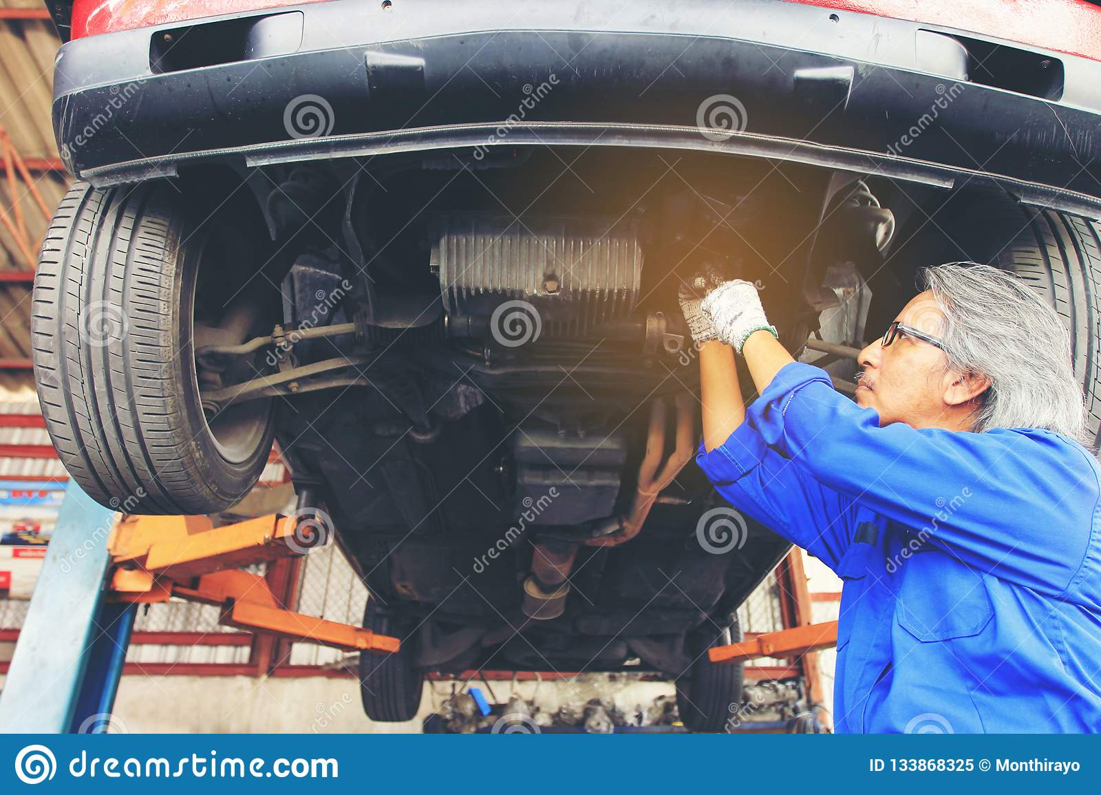 Close-up of car mechanic working under car in auto repair service.