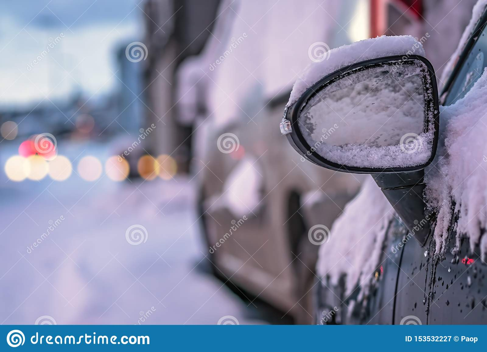 Close up of a car mirror covered in snow