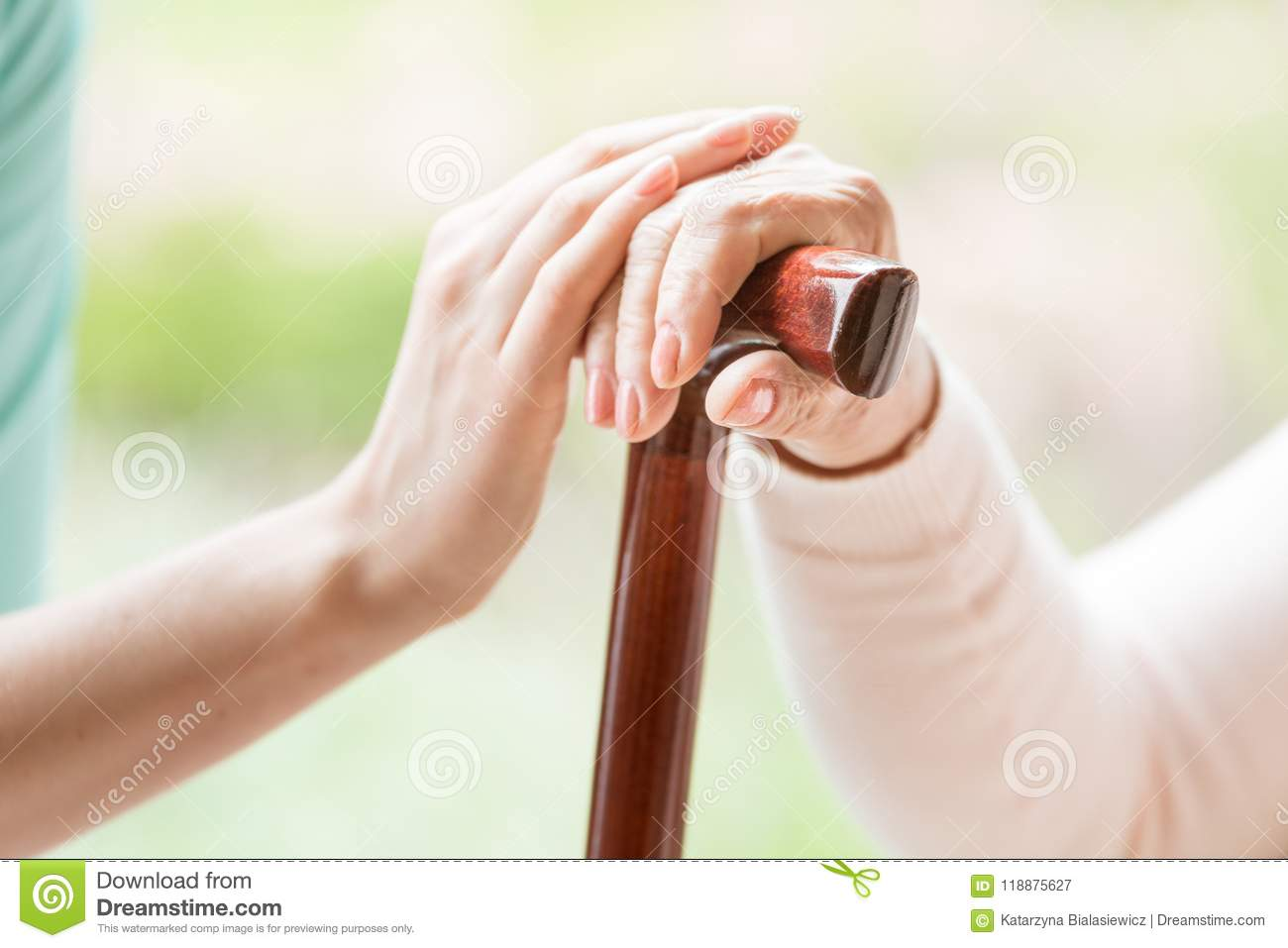 Close-up of caregiver holding hand of a senior person with walki