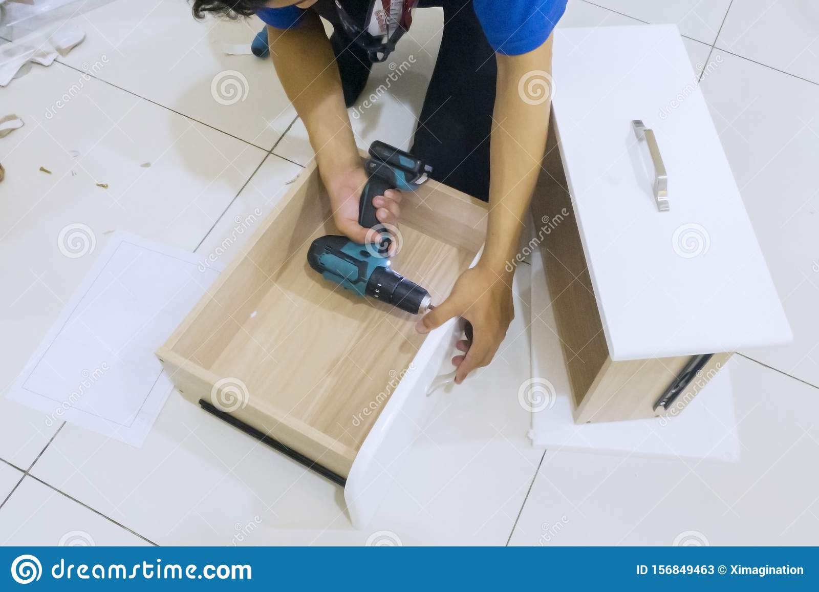 Carpenter hands installing a drawer with a drill