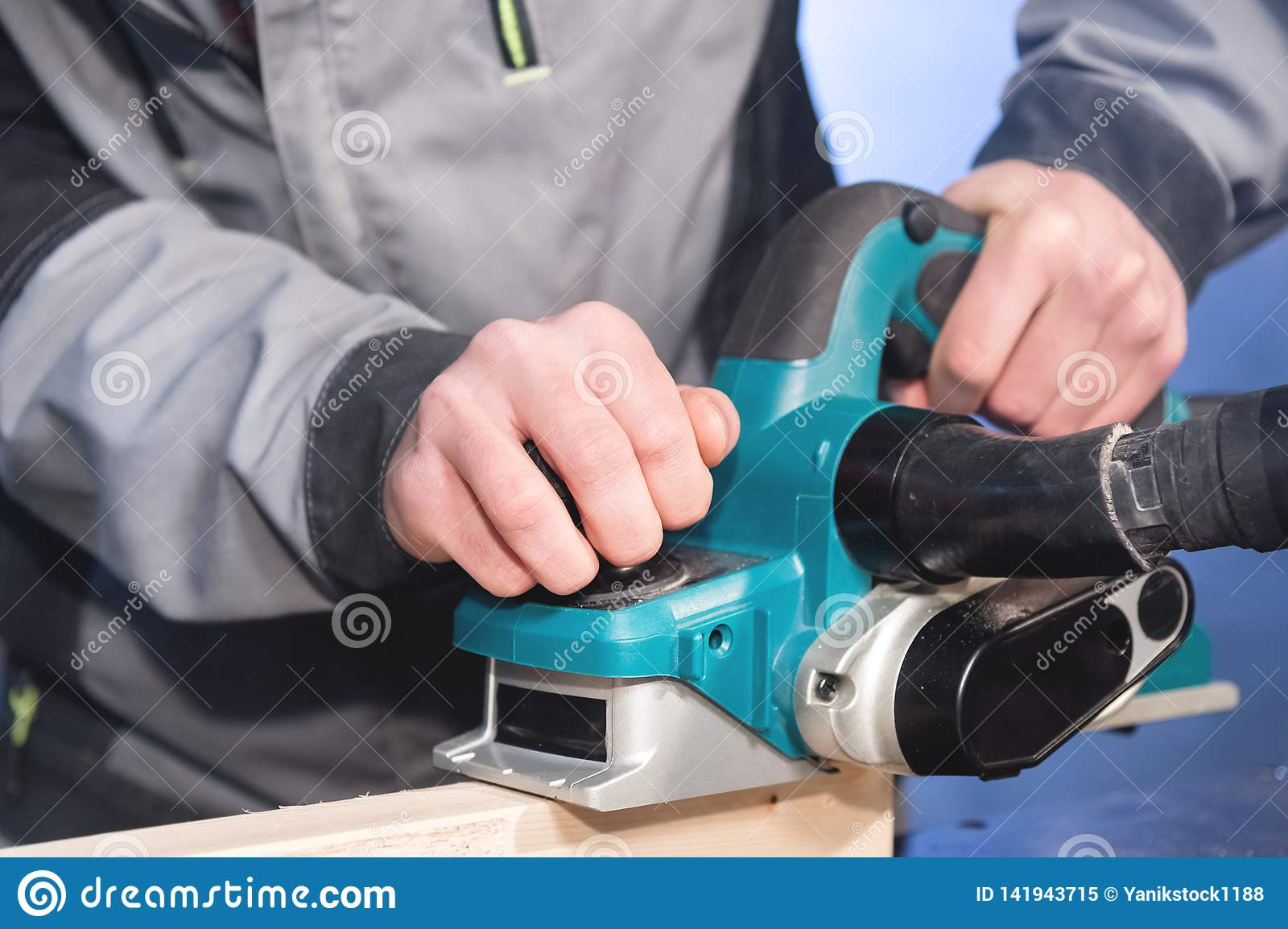 Close-up of a carpenter`s hand working with an electric plane with suction of sawdust. Leveling and sanding wooden bars