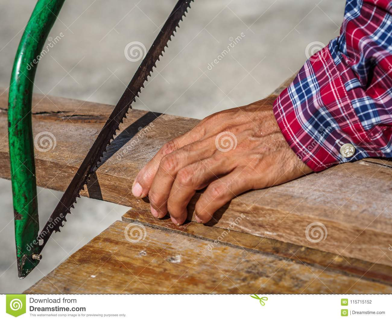 Download Close Up Of Carpenter Sawing A Board With A Hand Wood Saw. Profe Stock Photo - Image of helmet, lumber: 115715152