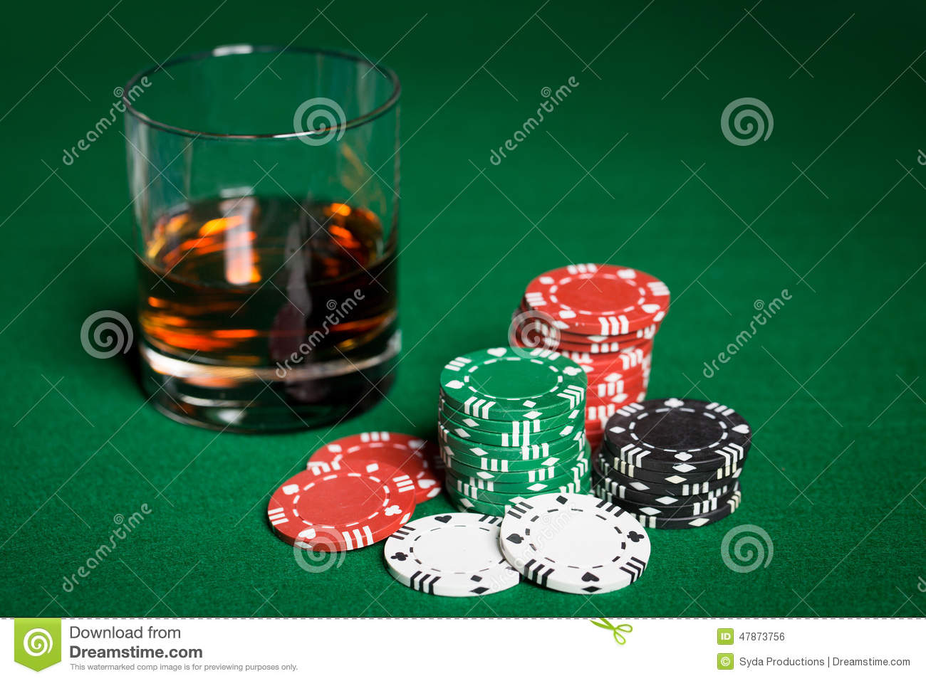 Close up of casino chips and whisky glass on table
