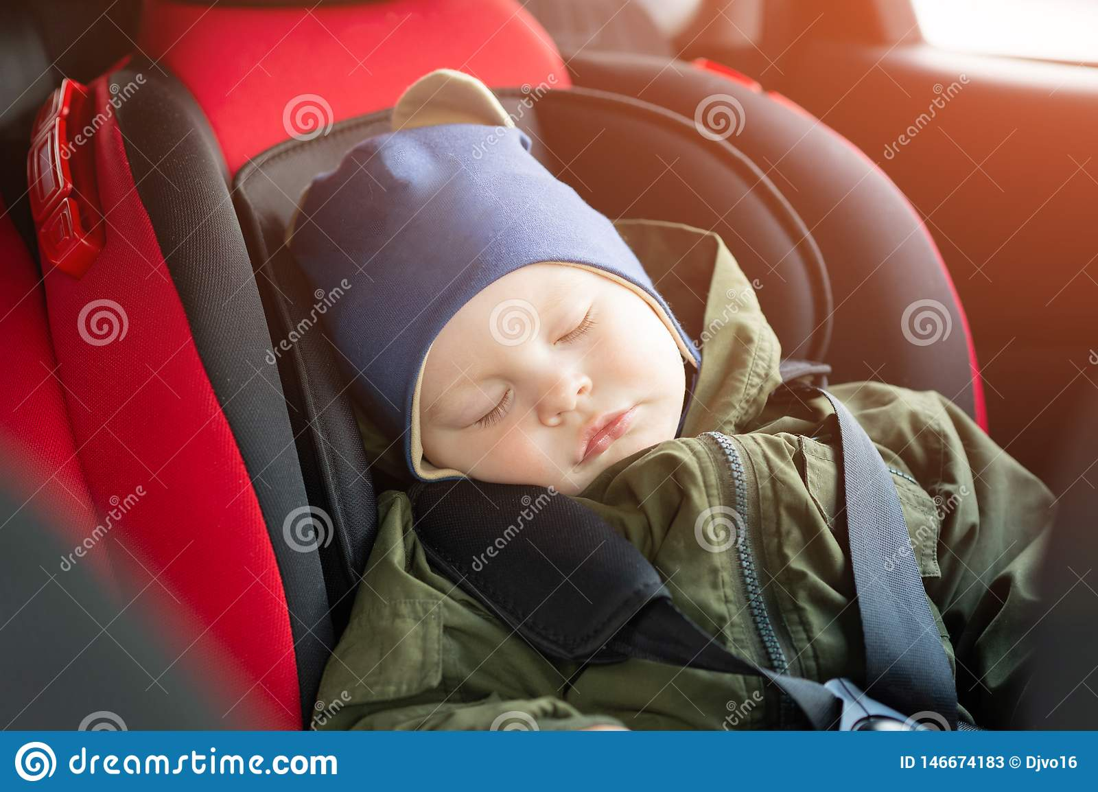Close Up caucasian cute baby boy sleeping in modern car seat. Child traveling safety on the road. Safe way to travel