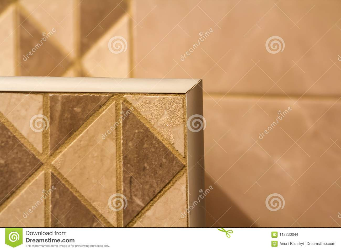 Close Up Of Ceramic Tiles Out Corner With Silver Metal Strip On The