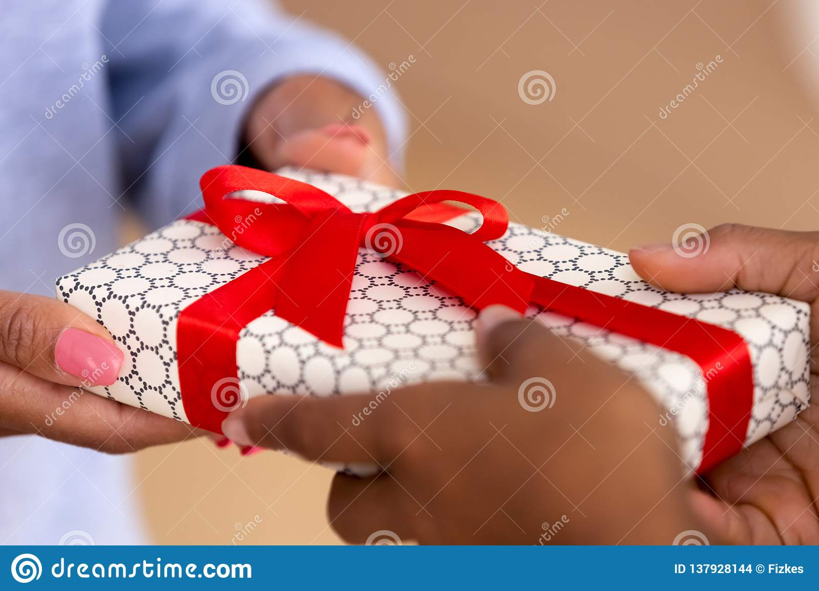 Close Up Of African American Child Holding Box Presenting Gift To Mother Or Friend Black Kid Make Surprise Giving Wrapped Present Mommy