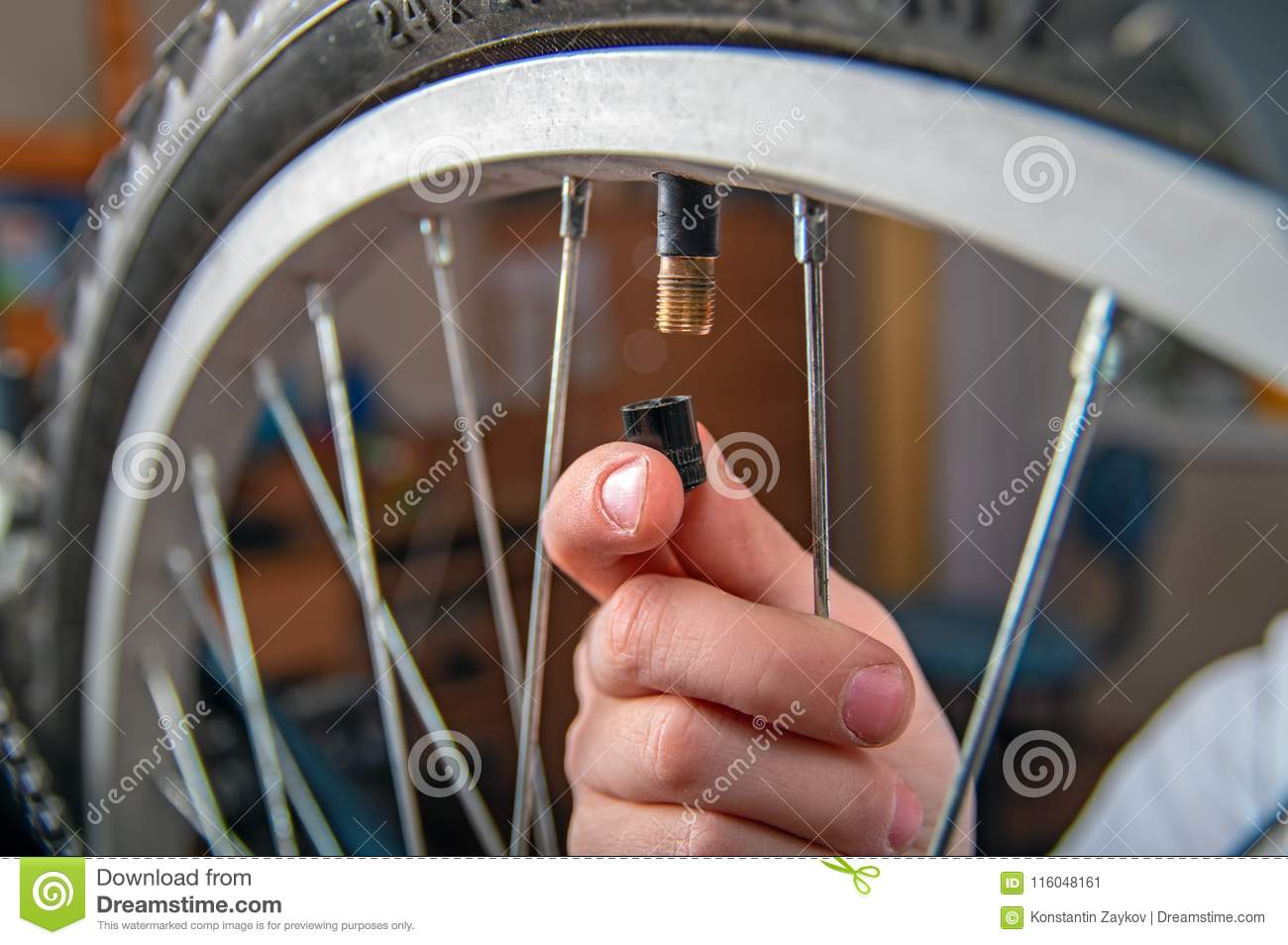 Close-up of child`s hand with cap for bicycle wheel nipple. Pumping tires bike.