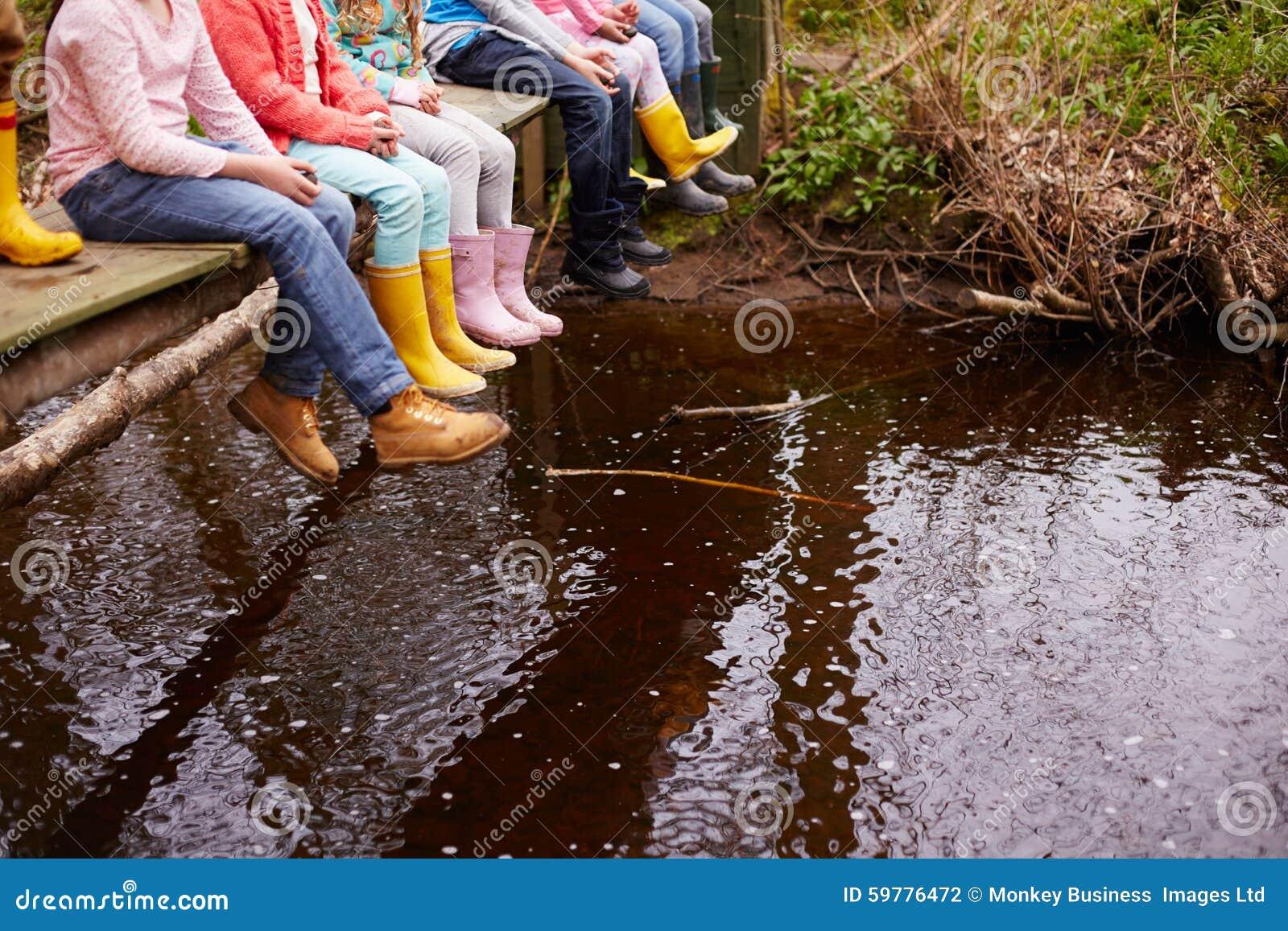 Close Up Of Children s Feet Dangling From Wooden Bridge