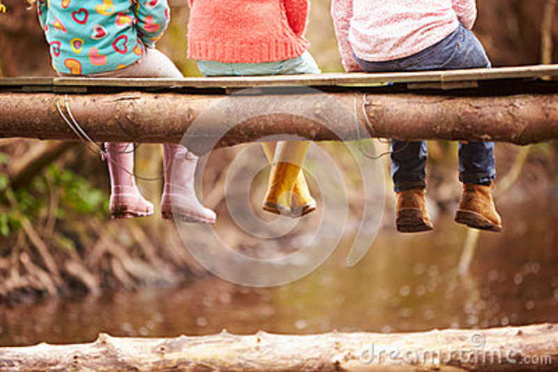 Close Up Of Children s Feet Dangling From Wooden Bridge