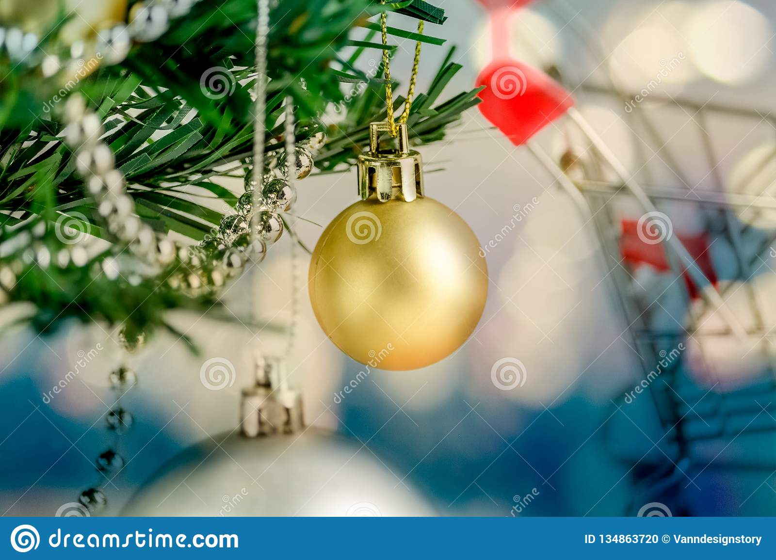 Close-up of Christmas tree is decorated with shopping cart for shopping and bokeh blue tone background, gold and silver balls on a