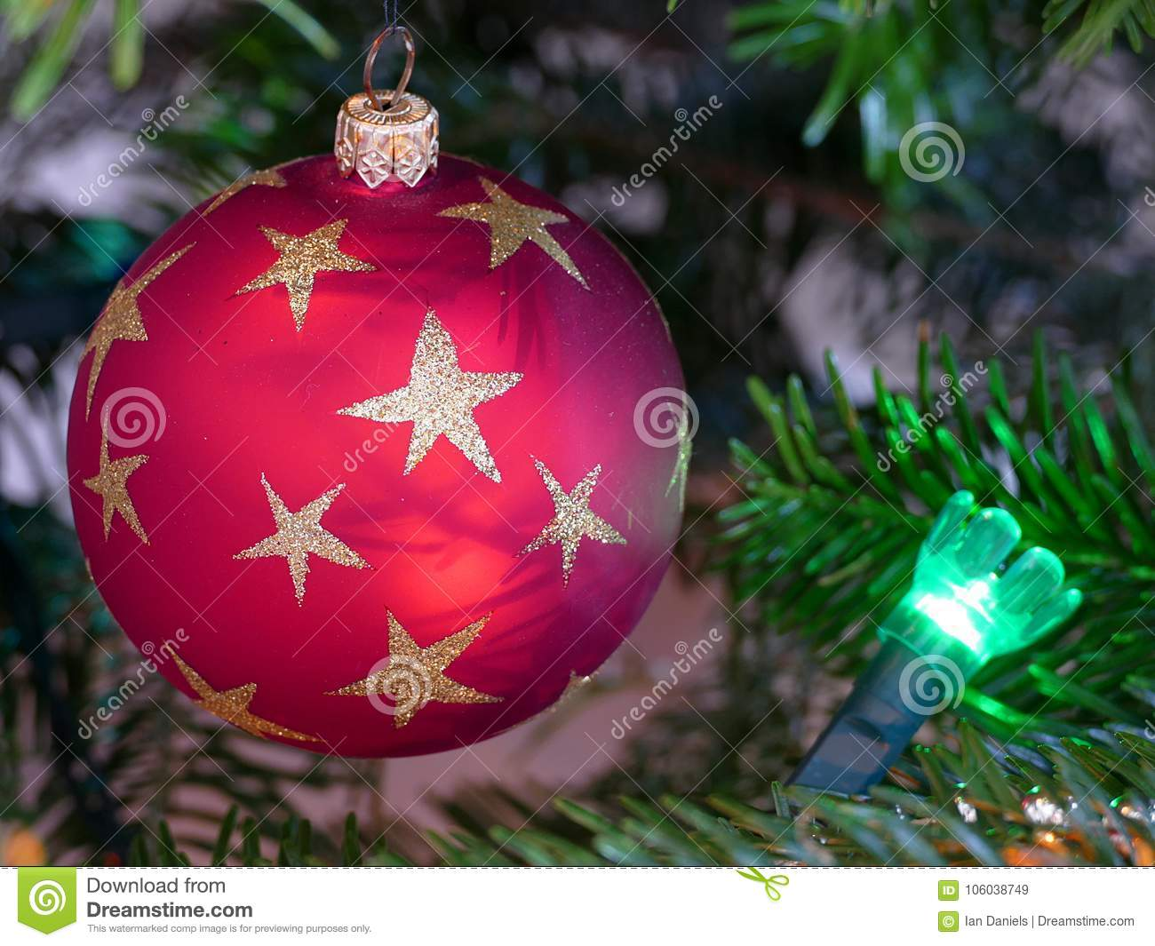 Close up of a circular red bauble on a Christmas tree with a green fairy light