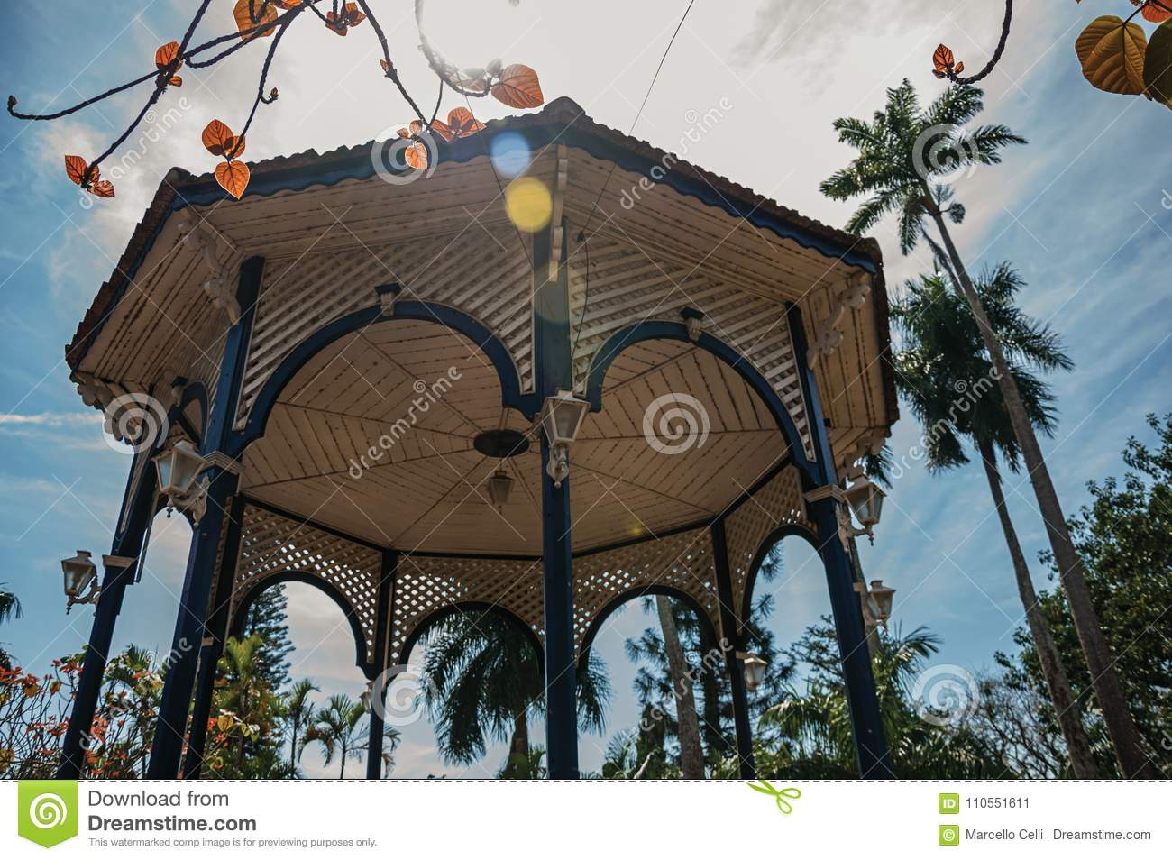 Close-up of colorful gazebo ceiling in the middle of garden full of trees, in a bright sunny day at São Manuel.