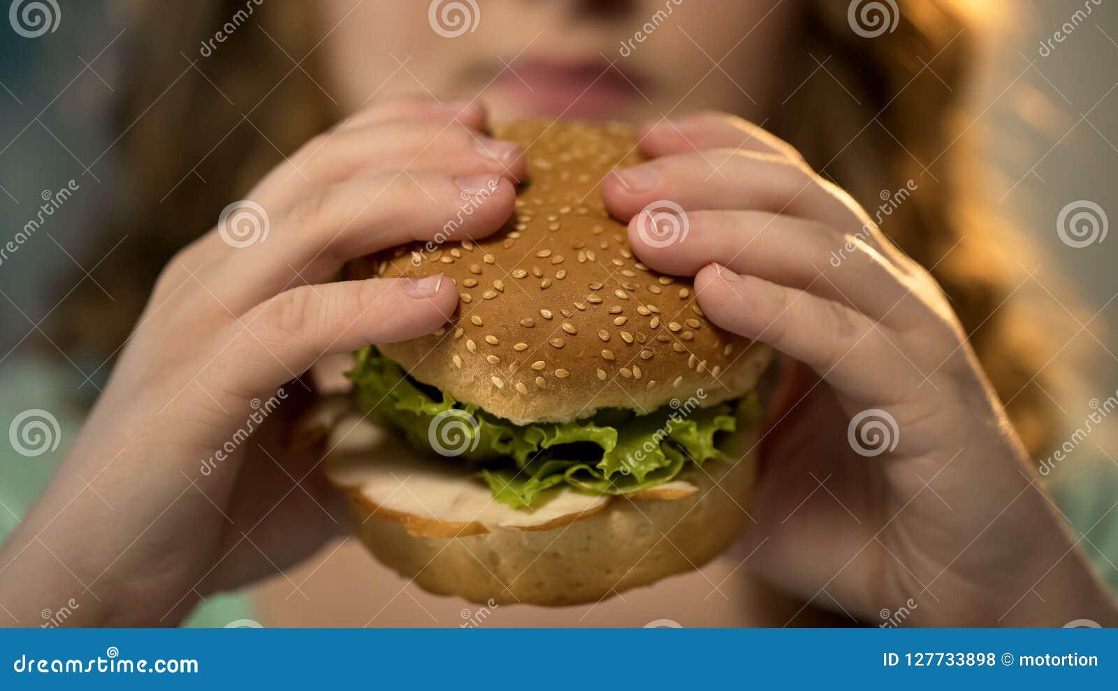 Close up cortante fêmea do hamburguer do fast food, nutrição insalubre e comer demais