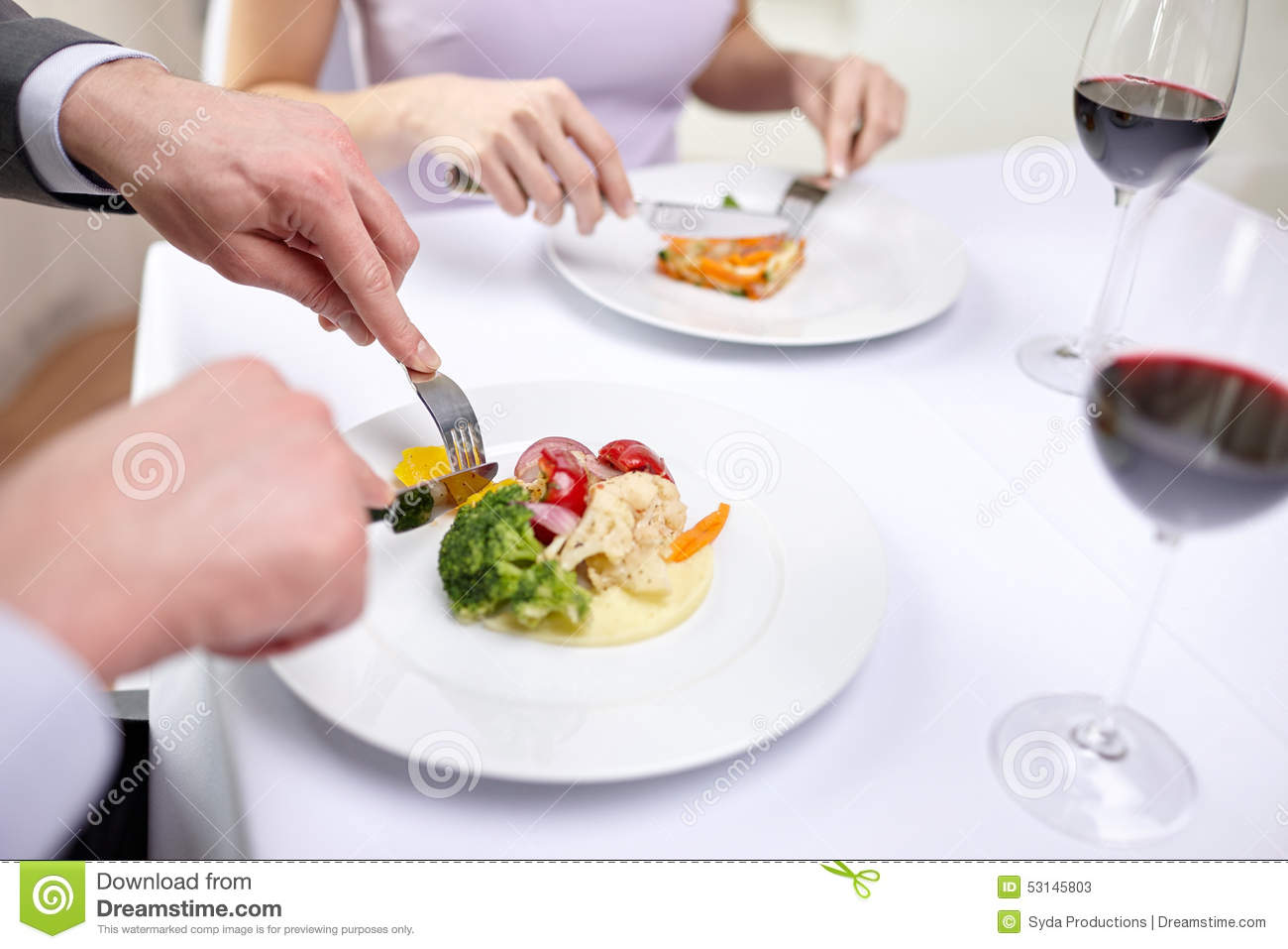 Close up of couple eating appetizers at restaurant