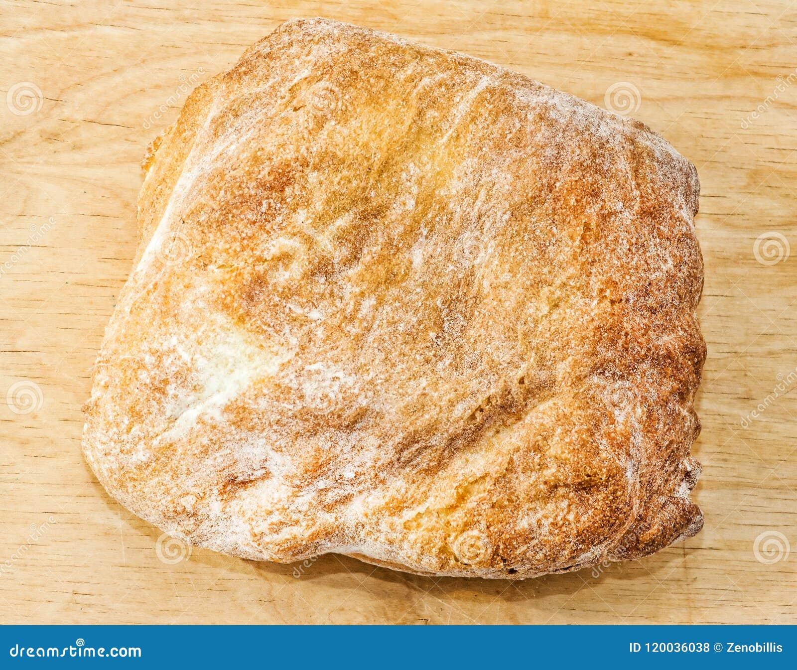 Close-up cozido fresco do pão italiano do ciabatta na placa de madeira Vista superior
