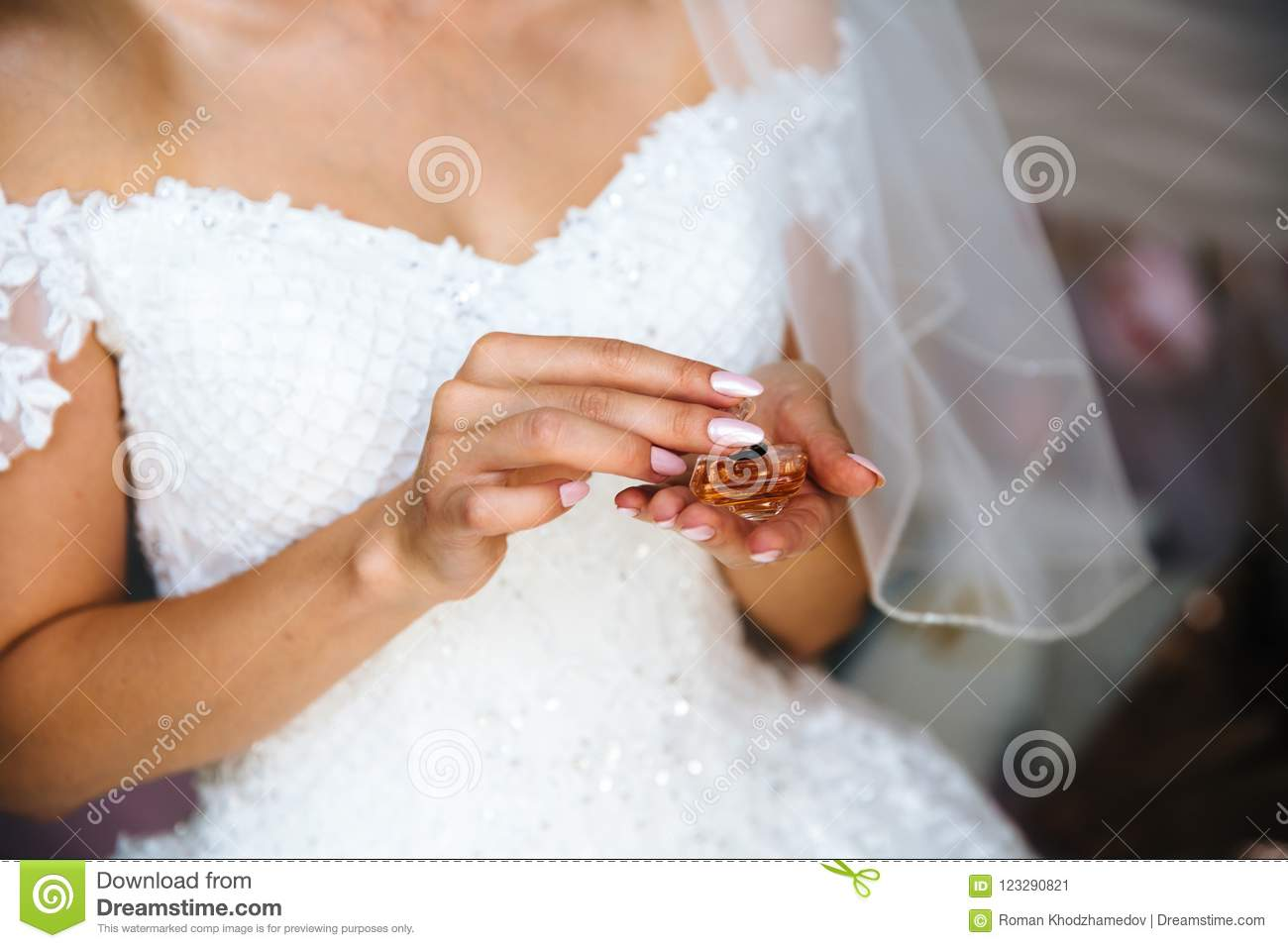 A Close Up Of A Cropped Bride In A Wedding Dress Is Holding A Small
