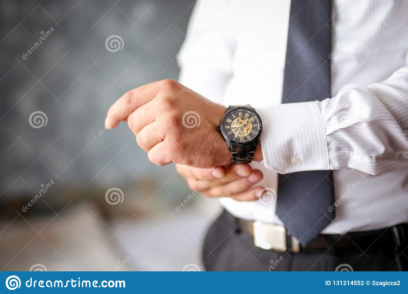 A close-up of a cropped frame of a man in an expensive classic costume looks at his watch.