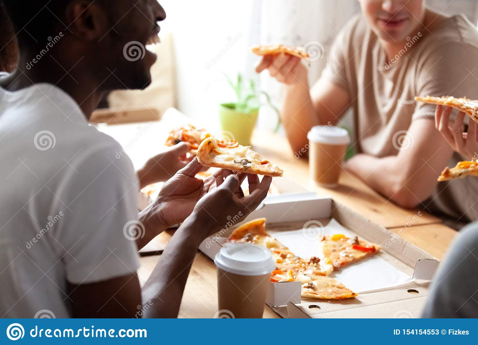 Close up cropped image of diverse friends eating pizza.