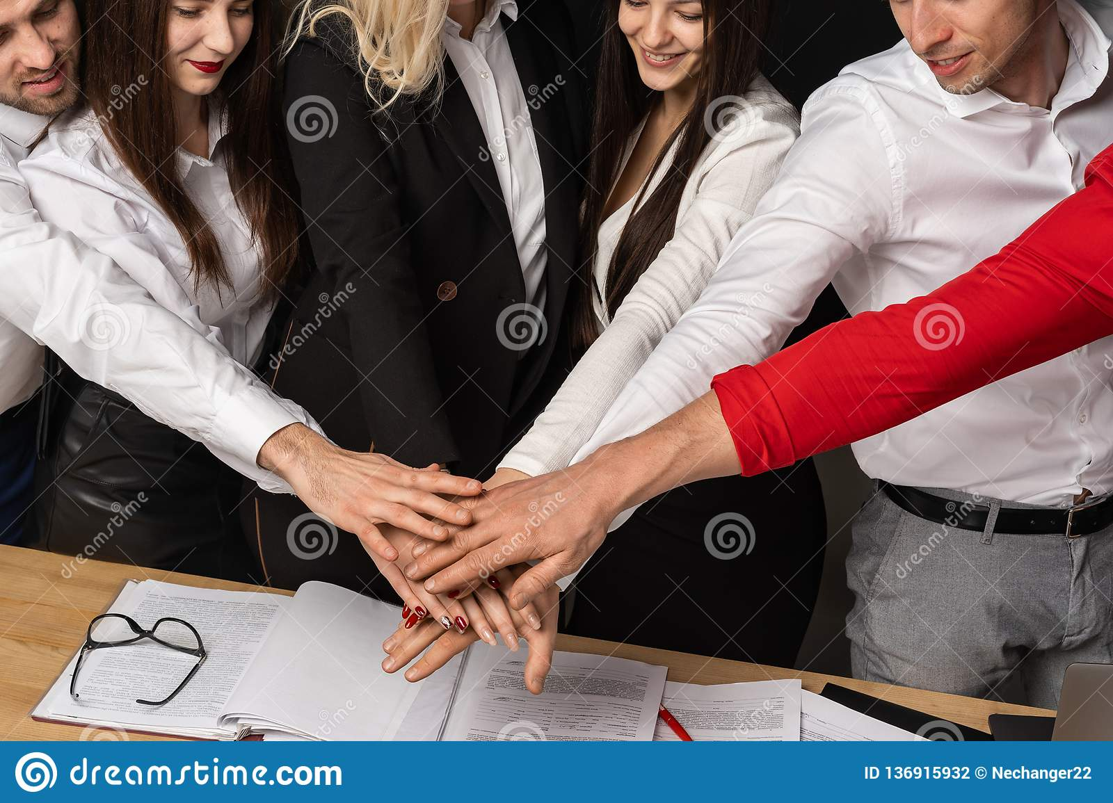 Close up cropped portrait of positive businesspeople putting arms together