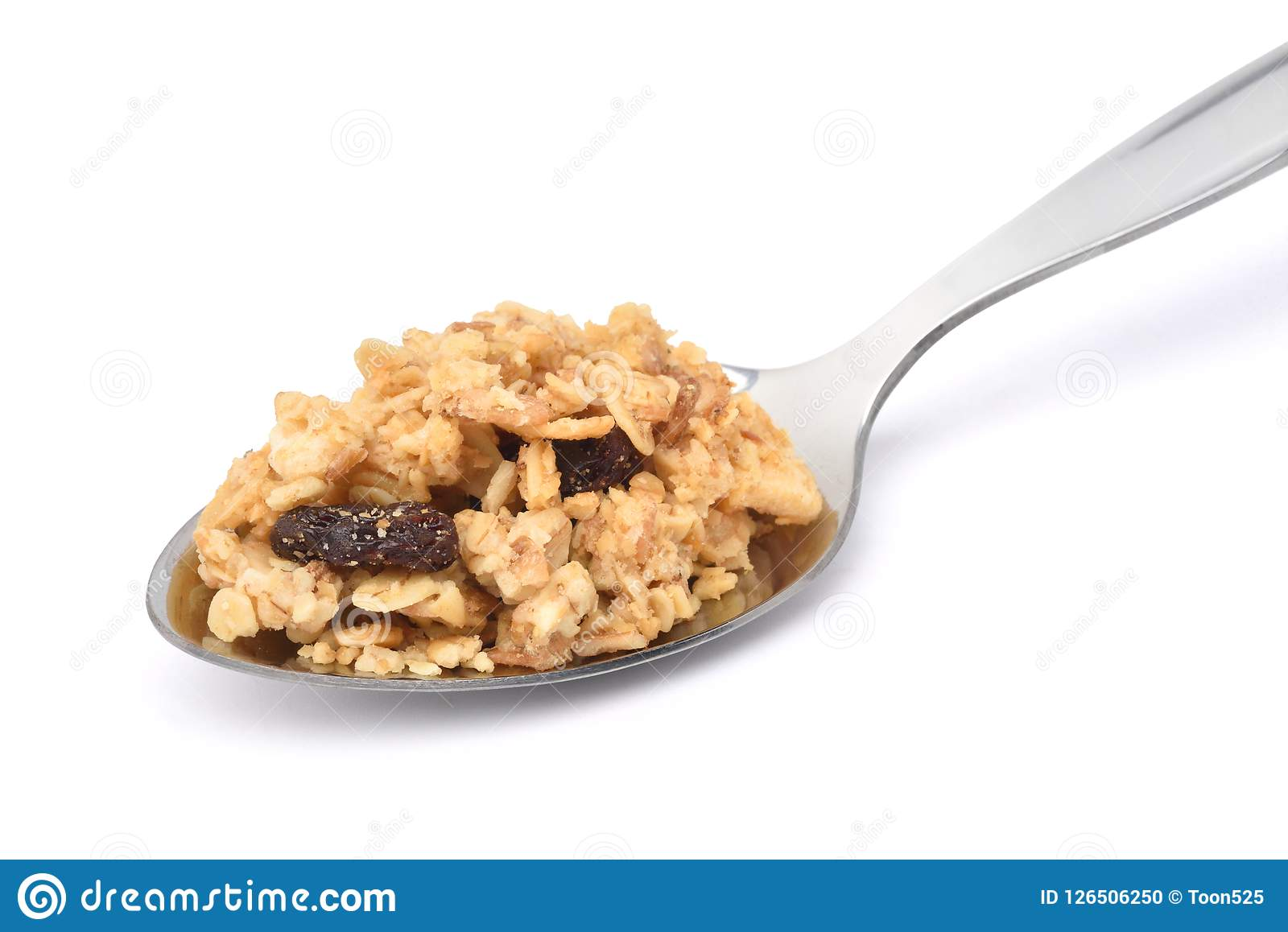 Crunchy oat granola cereal with dried fruits in stainless spoon