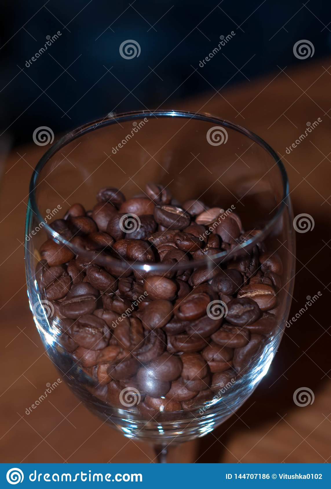 Close up of crystal wine glass with brown coffee beans