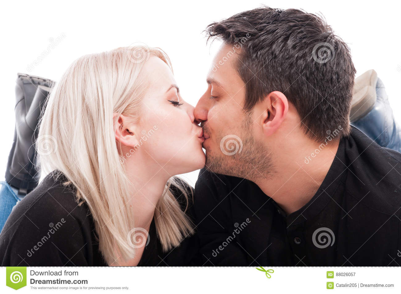 Close up of cute young couple kissing with passion on white studio background