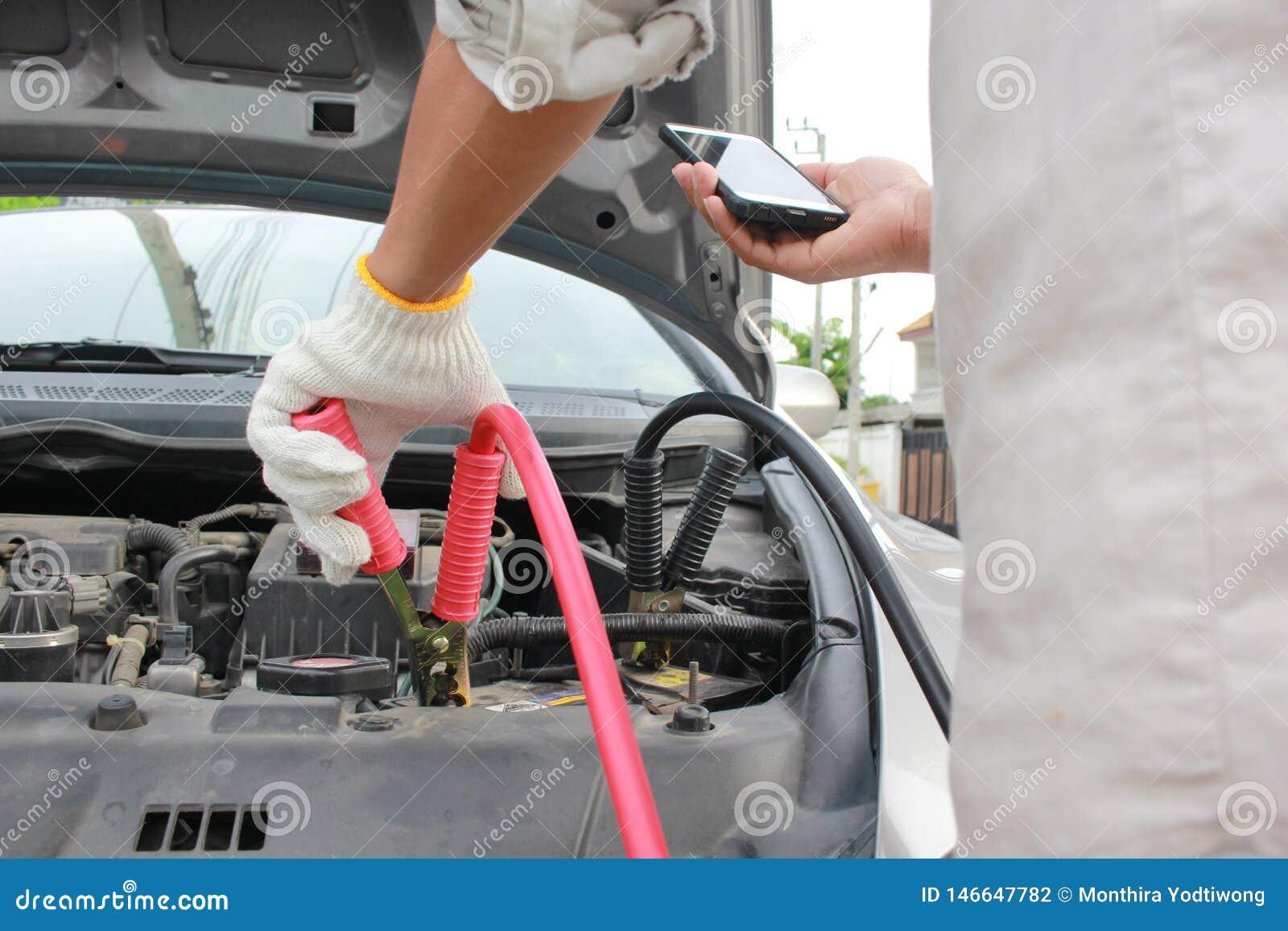 Close-up da bateria e do homem descarregados automóvel de carregamento que chamam ao serviço do mecânico de carro