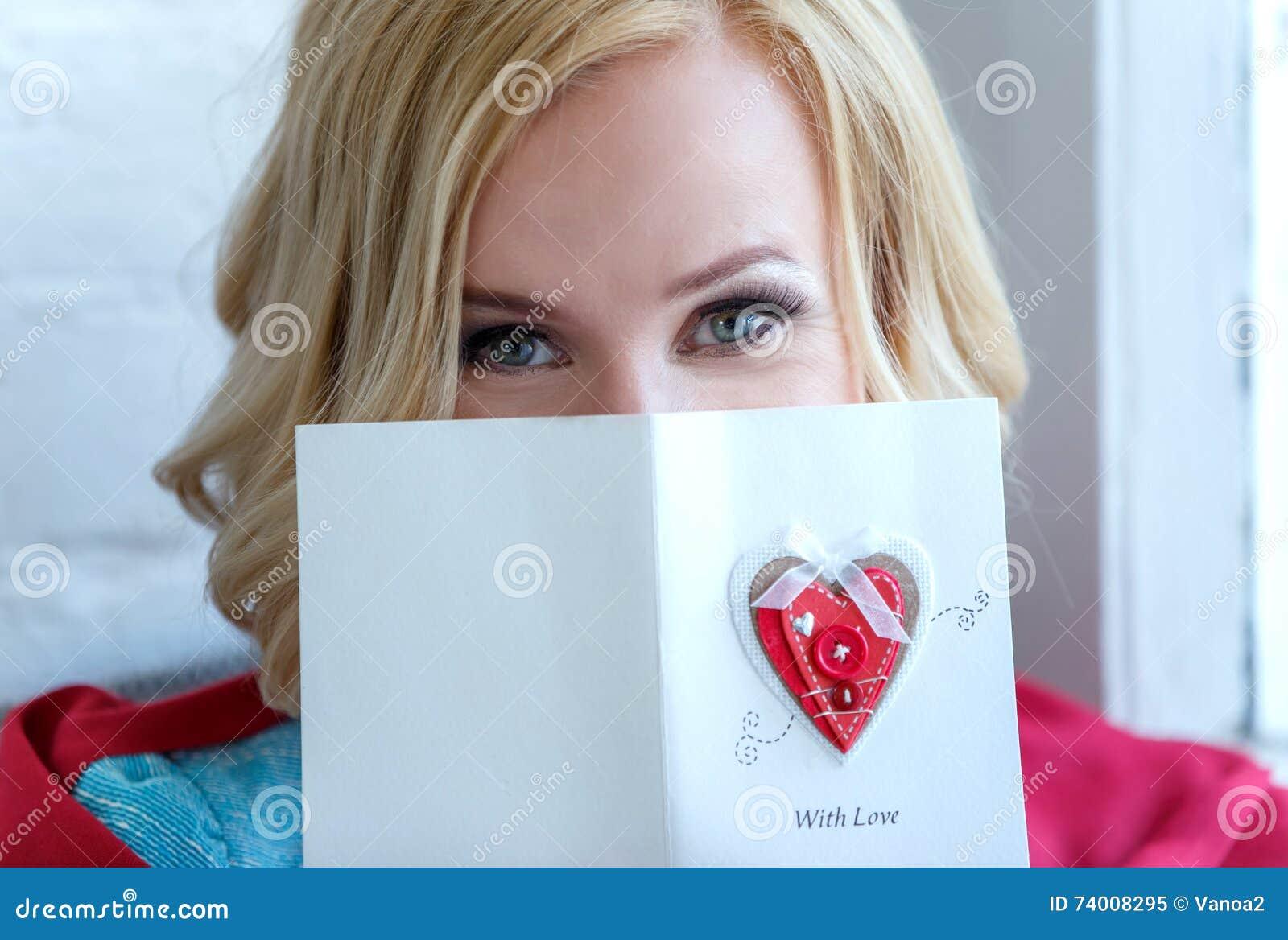 Close up da cara da mulher coberto em parte com o cartão do amor